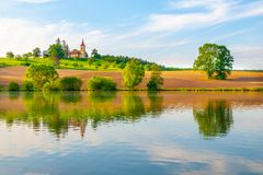 Free Romantic Landscape With Small Church On The Hill Reflected In The Pond. Sunny Summer Day With Blue Sky And White Clouds Stock Photo - 116906290