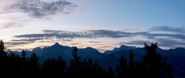 Romantic large panorama with alpine mountains and trees silhouet. Tes on sunset, view from Veysonnaz, Swiss Stock Photo