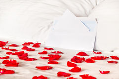 Romantic letter - envelope on a bed among rose petals Royalty Free Stock Photo