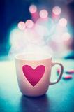 Romantic lifestyle with mug and heart at bokeh background, front view. Love symbol or Valentines day Royalty Free Stock Photo