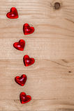 Romantic light wood background with glass hearts Stock Image