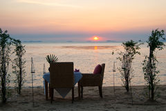 Romantic little table on the seashore, with candles. Stock Photos