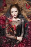 Romantic look. Interesting ginger model surrounded with feathers Royalty Free Stock Images