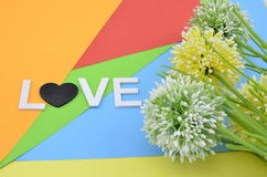 Romantic look with word love and symbol. artificial circle yellow, green and white flower on colourfull background Royalty Free Stock Photo