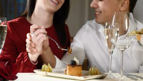 Romantic and love affairs. young couple on a date. A woman feeds her man with a delicious dessert. Couple laughing in a. Restaurant. Glasses of champagne on stock video footage