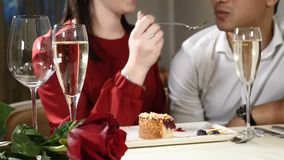 Romantic and love affairs. young couple on a date. A woman feeds her man with a delicious dessert. Couple laughing in a. Restaurant. Glasses of champagne on stock video