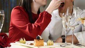 Romantic and love affairs. young couple on a date. A woman feeds her man with a delicious dessert. Couple laughing in a. Restaurant. Glasses of champagne on stock footage