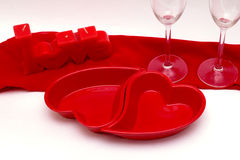 Romantic love dinner. Red plates in the shape of a heart and two glasses on a red and white background stock images