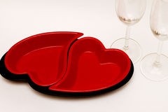 Romantic love dinner. Red plates in the shape of a heart and two glasses on white background royalty free stock photo