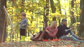 Romantic and love. Fall foliage. Cheerful family having picnic. Mother and father with son having fun outdoor. Happy. Autumn Family stock video footage