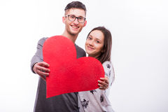 Romantic love hipster couple  with a red heart in hands look at camera. Royalty Free Stock Images