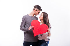 Romantic love hipster couple  with a red heart in hands look each other. Stock Photo