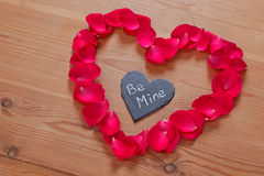 Romantic love message on slate in a rose petal heart. Red rose petals and slate in a heart shape with a romantic love message 'Be Mine Stock Image