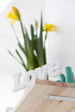 Romantic love sign on a shelf with flowers Royalty Free Stock Images
