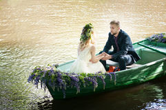 Romantic love story in boat. Woman with wreath and white dress. European tradition Royalty Free Stock Image