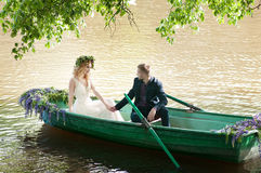 Romantic love story in boat. Woman with wreath and white dress. European tradition Stock Images