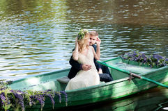 Romantic love story in boat. Woman with wreath and white dress. European tradition Royalty Free Stock Photos