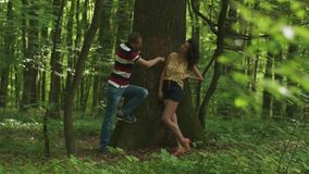 Romantic love story. Young beautiful couple in love carving a heart with their initials on a tree. Green spring forest. Background stock footage