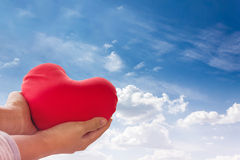 Romantic lovely valentine concept with hand gently raise up red. Heart on blue sky background Stock Images