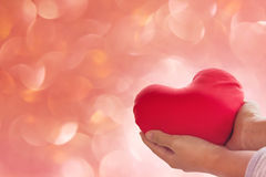 Romantic lovely valentine concept with hand gently raise up red. Heart on soft bokeh background Royalty Free Stock Photography