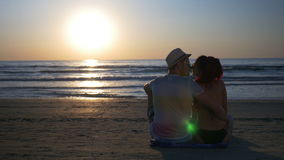 Romantic lovers on the beach hugging and kissing at twilight near the sea. Romantic lovers on the beach hugging and kissing at twilight with the sea on the stock video footage