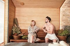 Beautiful couple relaxing in sauna and caring about health and skin. Romantic lovers having a body care day in steam bath royalty free stock photo
