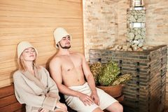 Beautiful couple relaxing in sauna and caring about health and skin. Romantic lovers having a body care day in steam bath - Concept of healthy and vacation stock photography