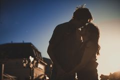 Romantic  lovers hugging at twlilight with sunset in background Stock Photo