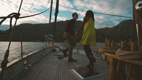 Romantic loving couple dancing on yacht sunset outdoors. Beautiful woman with dark skinned hair mulatto yellow dress smiling dance enjoy music. man in shirt stock video footage