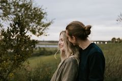 Romantic and Loving Young Adult Couple at the Park Looking At Nature and the Horizon for Portrait Pictures stock images