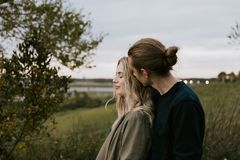 Romantic and Loving Young Adult Couple at the Park Looking At Nature and the Horizon for Portrait Pictures stock photography
