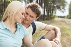 Romantic male hiker looking at woman while relaxing in forest Stock Images