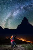 Romantic male tourist embracing red-haired girl and shows on stars and Milky way in beautiful starry sky at night. Against silhouettes of the high mountains and Royalty Free Stock Photos