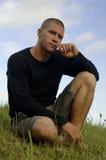 Romantic man. Sitting in a grass field Stock Photos