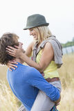 Romantic man carrying woman in field Royalty Free Stock Image