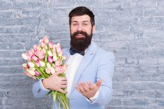 Romantic man with flowers. Romantic gift. Macho getting ready romantic date. Tulips for sweetheart. Man well groomed. Tuxedo bow tie hold flowers bouquet. How royalty free stock image
