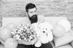 Romantic man with flowers and teddy bear sit on couch with air balloons waiting girlfriend. Romantic gift. Macho ready