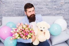 Romantic man with flowers and teddy bear sit on couch with air balloons waiting girlfriend. Romantic gift. Macho ready. Romantic date. Man wear tuxedo bow tie stock image