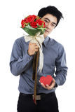 Romantic man with a gift box and flowers Stock Image