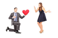 Romantic man giving a red heart to a young woman Stock Photography