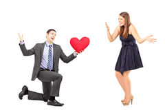 Romantic man giving a red heart to a young woman Royalty Free Stock Photo
