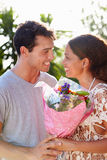 Romantic Man Giving Woman Bunch Of Flowers Stock Photography
