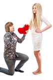 Romantic man on his knees holding a red heart and an excited blo Stock Photography