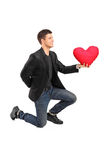 A romantic man on his knees practicing a proposal Royalty Free Stock Images