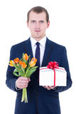 Romantic man holding gift box and flowers. Isolated on white background Royalty Free Stock Photo