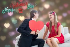 Romantic man holding pink heart and proposing girl Stock Photos