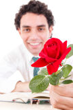 Romantic man holding rose with book and glasses on table Royalty Free Stock Photos