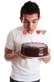 Romantic man kissing heart on a cake Royalty Free Stock Photography