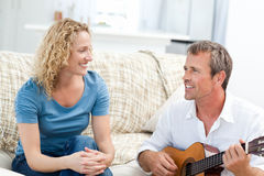 Romantic man playing guitar for her wife at home Royalty Free Stock Images