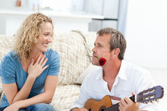 Romantic man playing guitar for her wife at home Stock Images